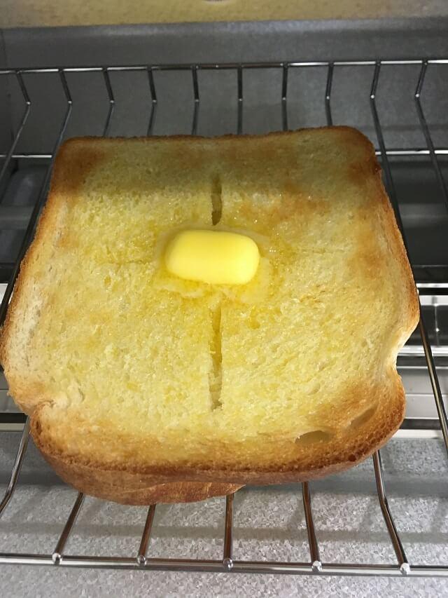 焼きたてパンの上にバターをのせる